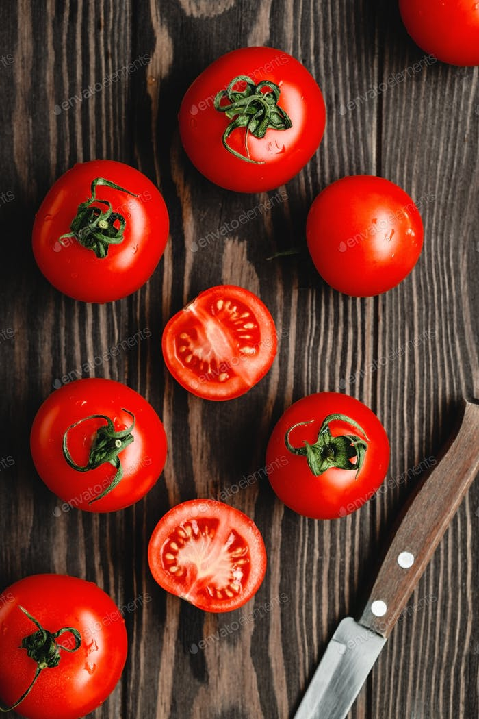 Ripe tomatoes on a wooden background. Top view, flat lay composition.