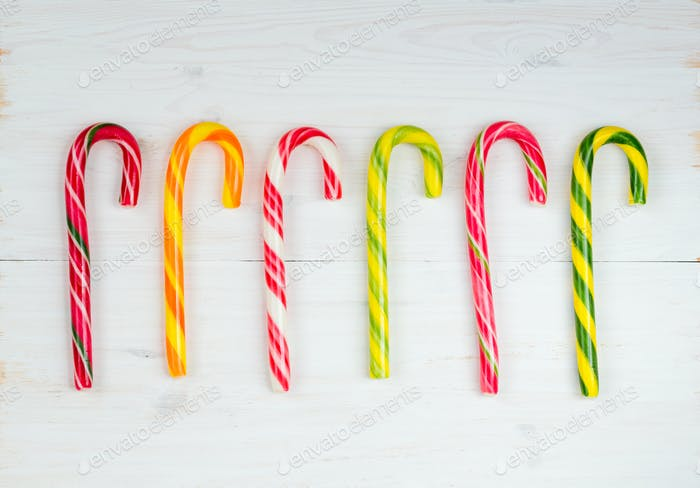 Christmas candy cane on a white wooden background