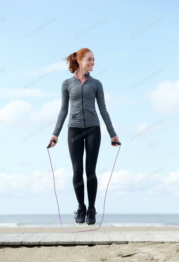 Woman exercising with jump rope outdoors