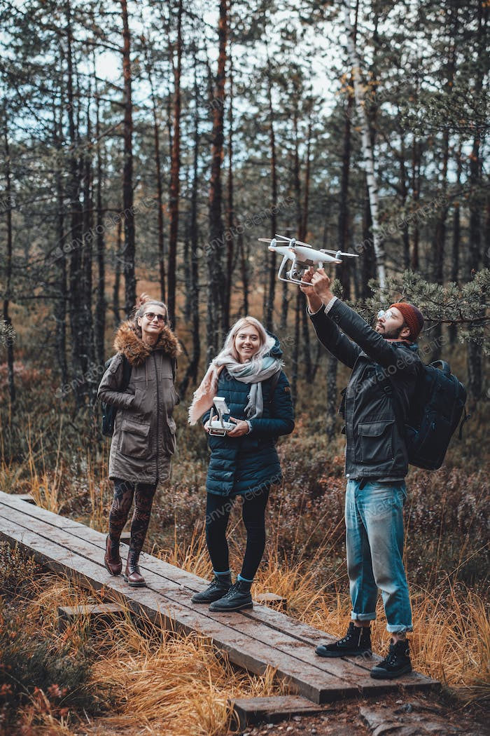 Three students on wooden road in autumn forest with quadcopter