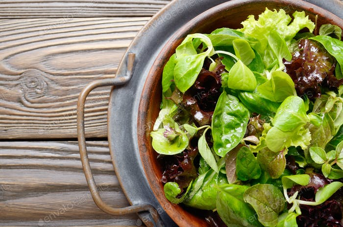Top view at clay dish with green and violet lettuce, lamb's lettuce salad
