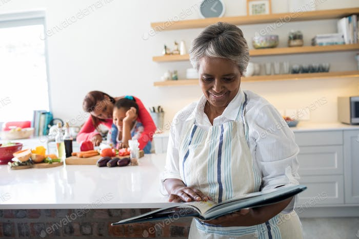 Grandmother looking at recipe book while mother and daughter chopping vegetables