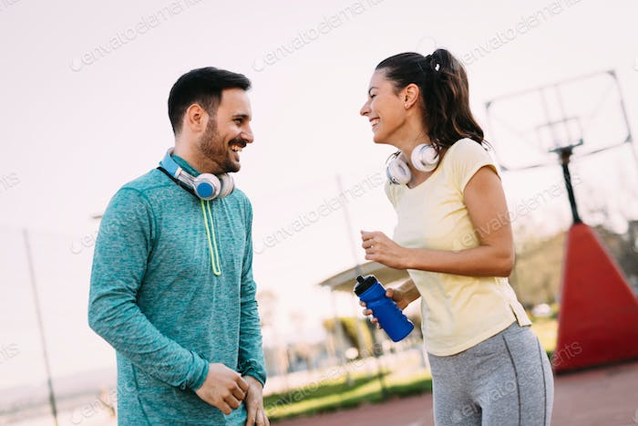 Handsome man and attractive woman talking on court