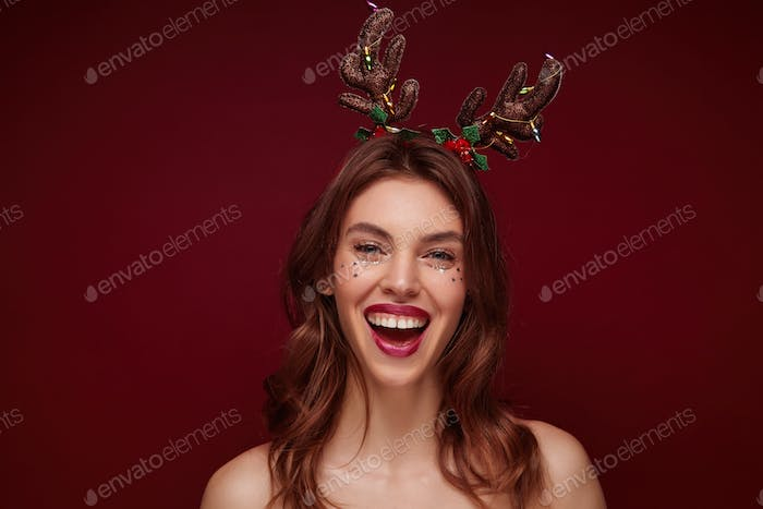 Close-up of joyful attractive young brunette lady with wavy hairstyle wearing holiday horns
