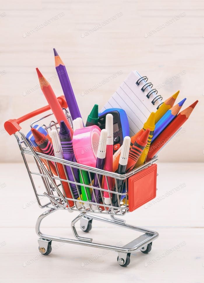 School supplies shopping trolley on natural wood background