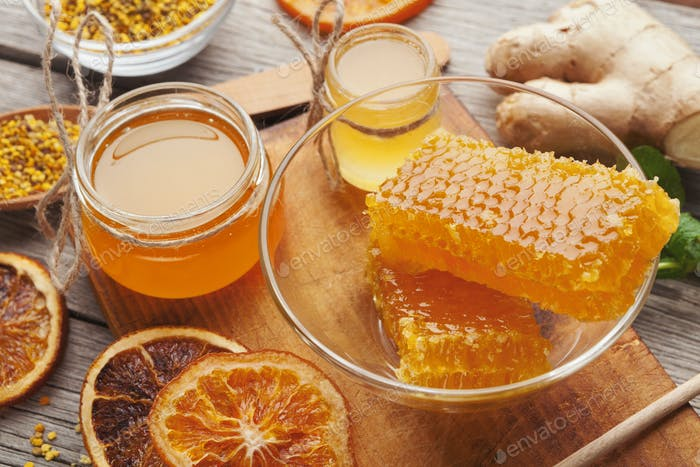 Various types of honey on wooden platter, closeup