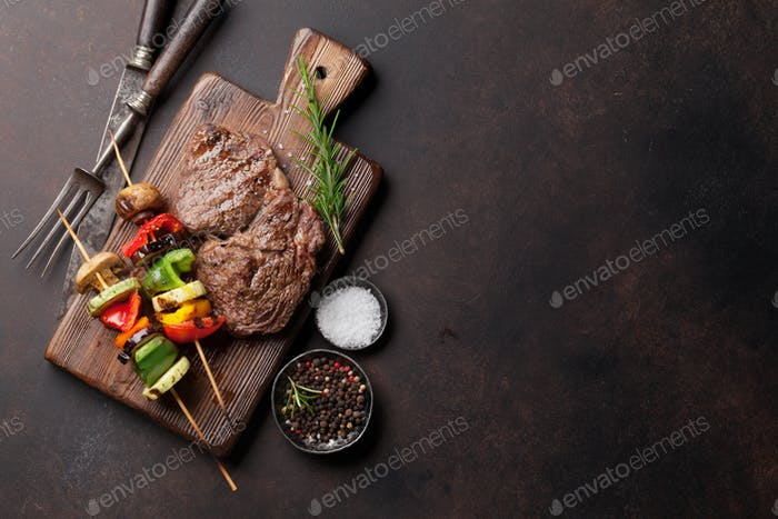 Grilled vegetables and beef steak on cutting board