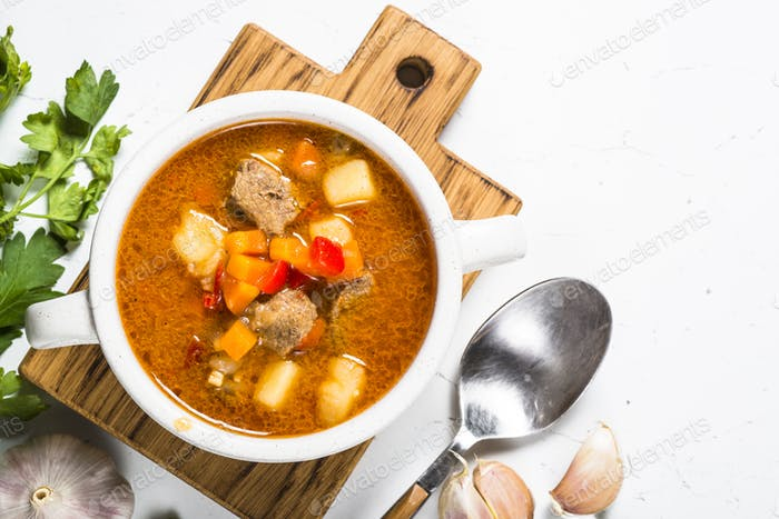 Goulash soup on white stone table top view