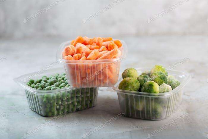 Verduras congeladas como guisantes verdes, coles de Bruselas y zanahoria bebé en las cajas de plástico