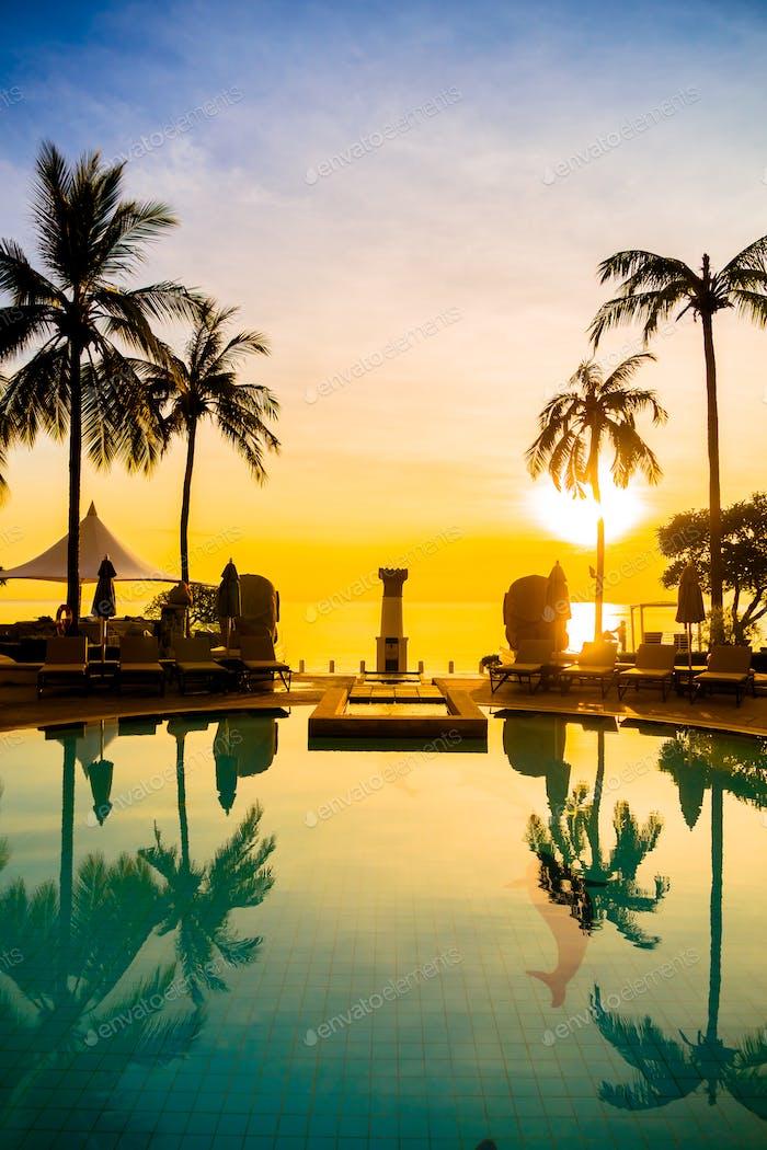 Silhouette coconut palm tree around swimming pool