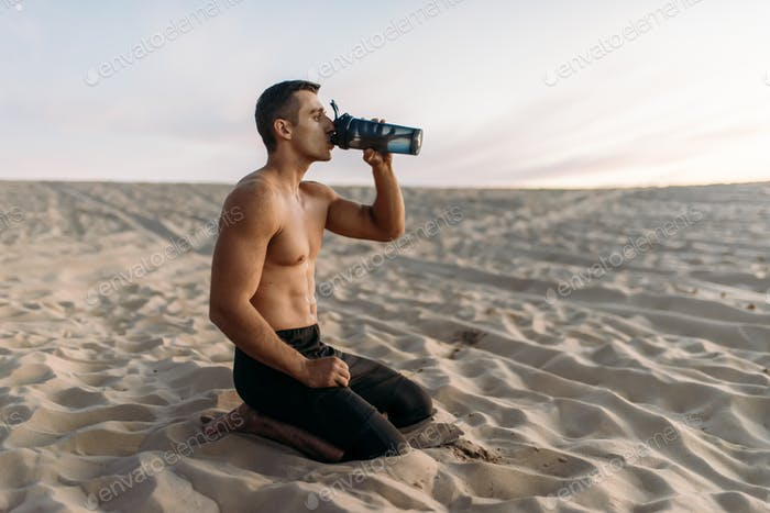 Male athlete drinks water after workout in desert