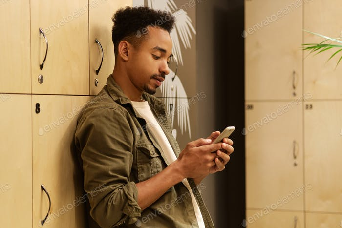 Young handsome casual African American guy thoughtfully using cellphone in locker room