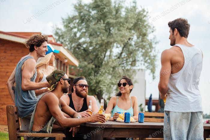 Smiling young people sitting and drinking together in summer