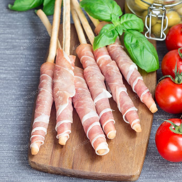Grissini bread sticks coiled with prosciutto ham on a wooden boa