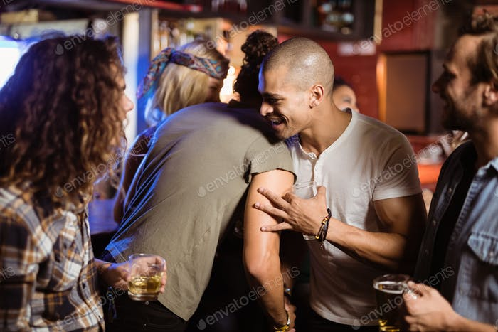 Smiling friends embracing at nightclub