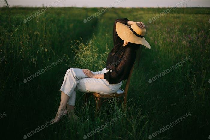 Langsam leben. Stilvolle elegante Mädchen in Strohhut sitzen auf rustikalen Stuhl