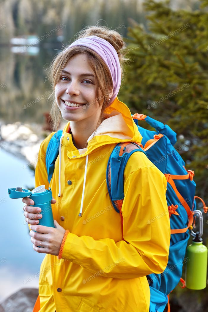 Lovely woman with glad facial expression, dressed in yellow raincoat, carries rucksack, holds thermo