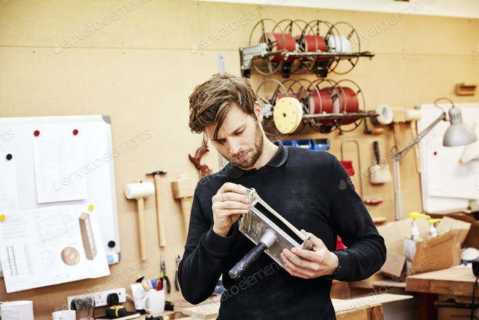 A furniture workshop.  A young man holding an object and examining it closely.