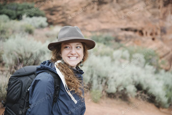 Smiling woman with auburn hair, wearing a hat and carrying a backpack, hiking in a canyon.