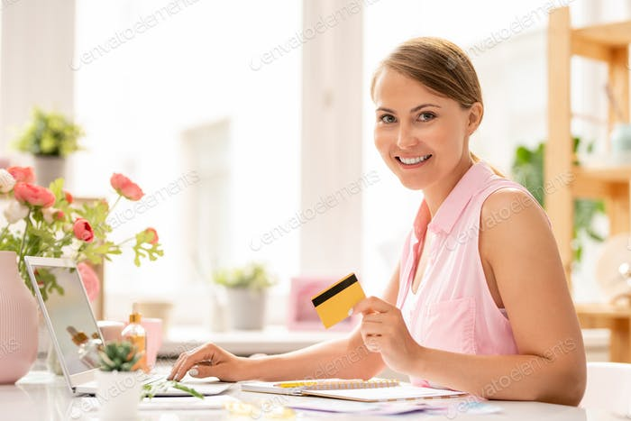 Happy young attractive woman with plastic card making online order