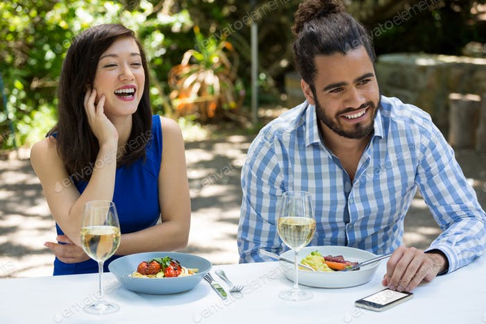 Cheerful couple having lunch at outdoor restaurant