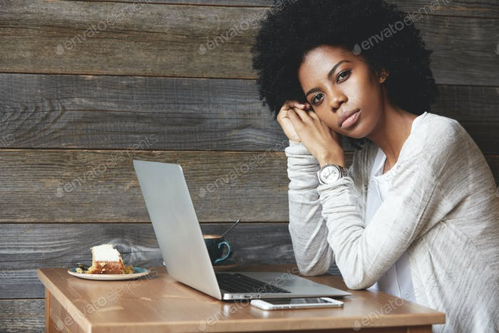 People and lifestyle concept. Beautiful African woman with Afro haircut wearing stylish clothes, loo