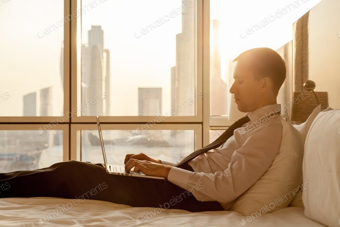 Young businessman working on laptop in bed