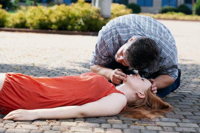 Schöner Mann lehnte sich über eine Frau auf der Straße liegend und ihre Lebensfunktionen überprüfen