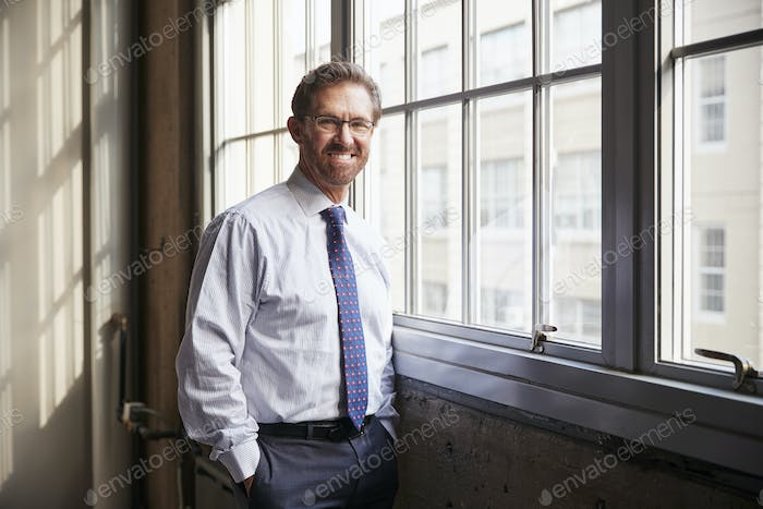 Senior businessman with hands in pockets smiling to camera