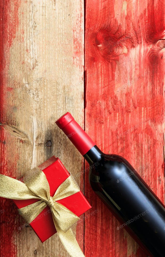 Valentines day. Red wine bottle and a gift on wood