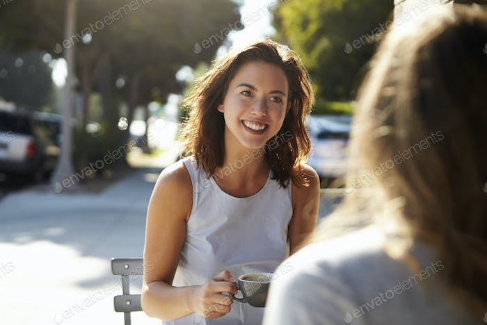 Two female friends talking over coffee outside a cafe