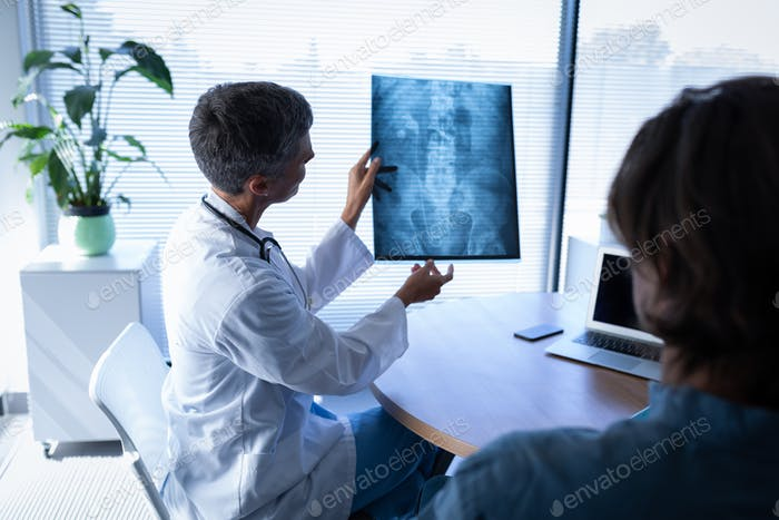 Female doctor showing x-ray report to disabled patient in clinic at hospital