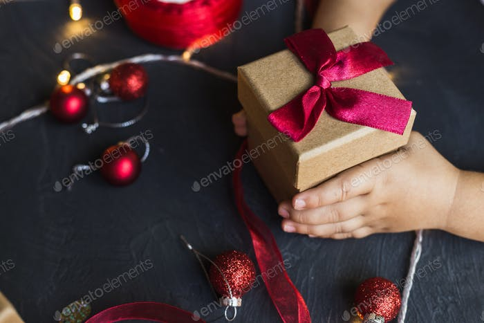 A child holds a Christmas gift box in his hands.