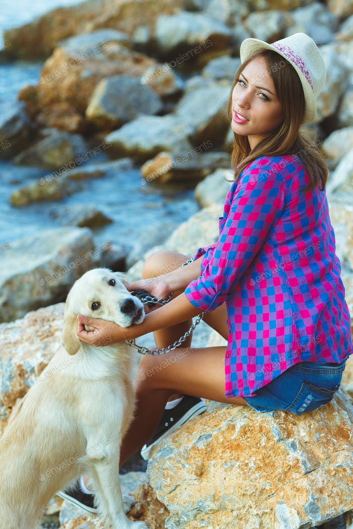 Woman with a dog on a walk on the beach