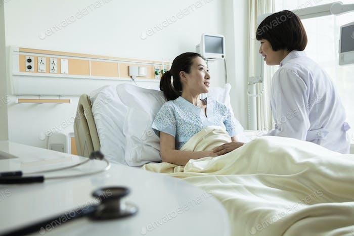 Ärztin sitzt auf dem Krankenhausbett und diskutieren mit jungen Patientin