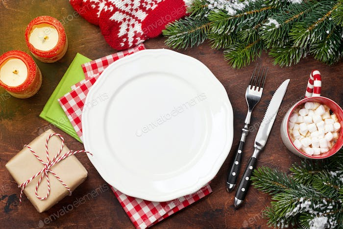 Christmas table setting with candles and xmas gift