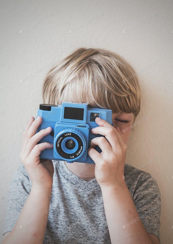 Junge mit Spielzeugkamera