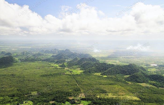 Luftaufnahme von großen Hügeln und brennenden Feldern in Belize