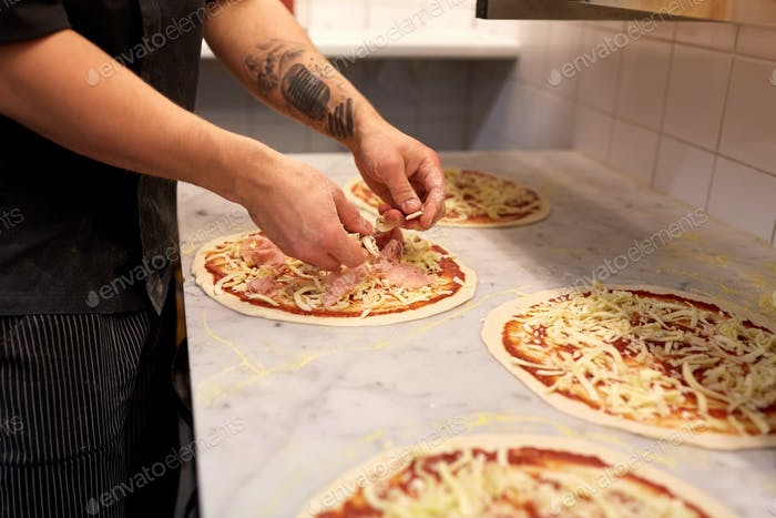 cook hands adding champignons to pizza at pizzeria