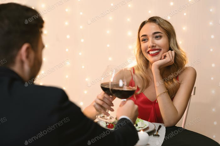 Romantic couple dining in restaurant, drinking wine and enjoying evening together
