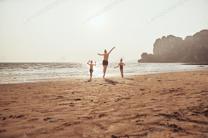 Mother and children skipping on a sandy beach during vacation