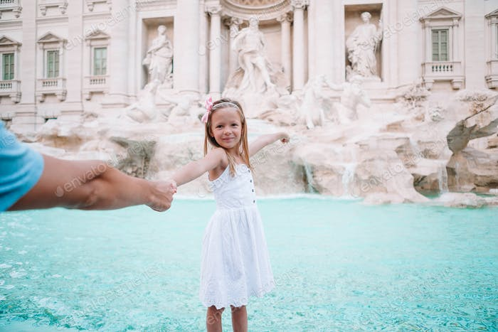 Adorable little girl background Trevi Fountain, Rome, Italy. Happy toodler kid enjoy italian