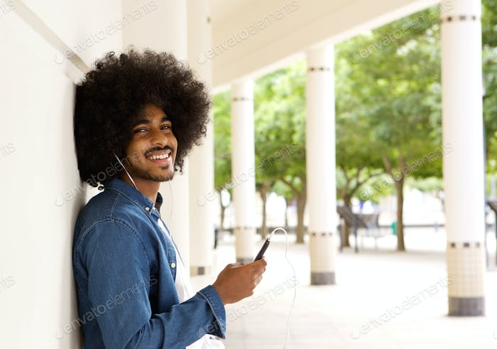 Cool black guy standing outside with mobile phone