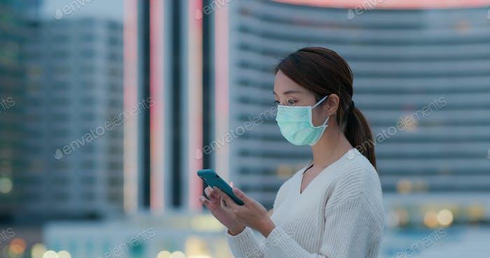 Frau tragen medizinische Gesichtsmaske und Verwendung von Handy in der Stadt bei Sonnenuntergang