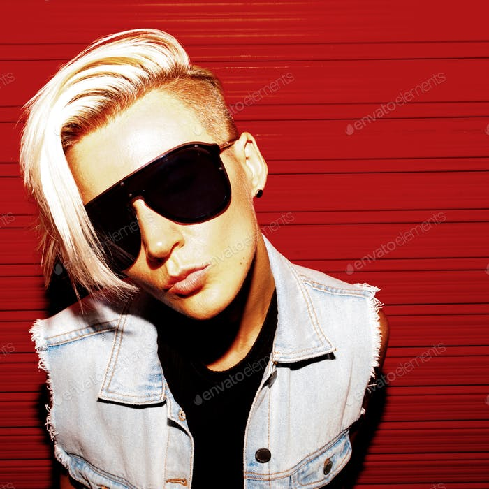 Girl with short hair in stylish clothes and sunglasses on a red