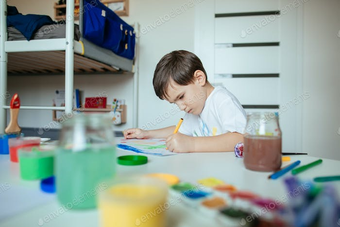 Child draws with left hand and concentrating.