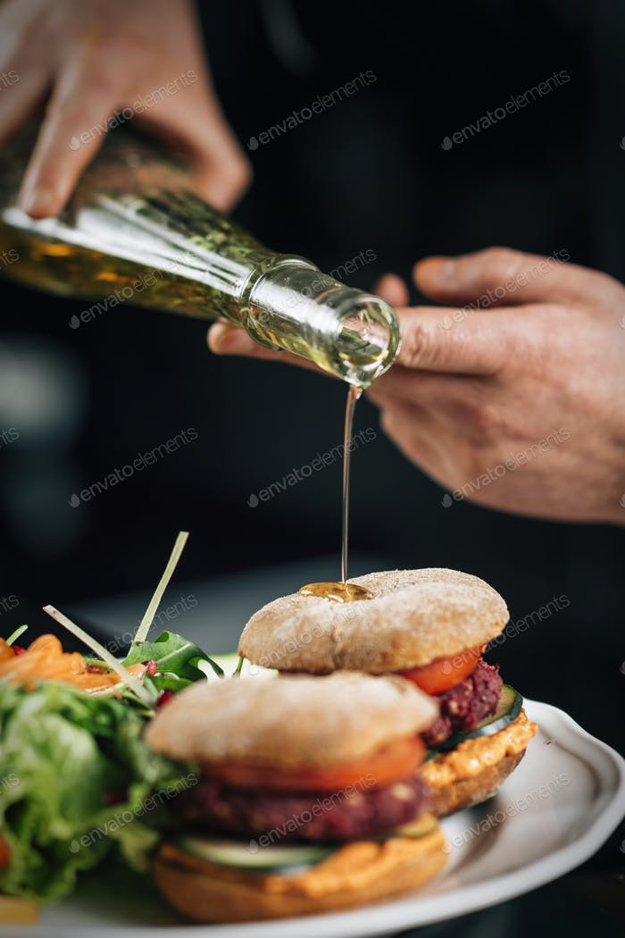 Chef Pouring Olive Oil onto a Vegan Burger