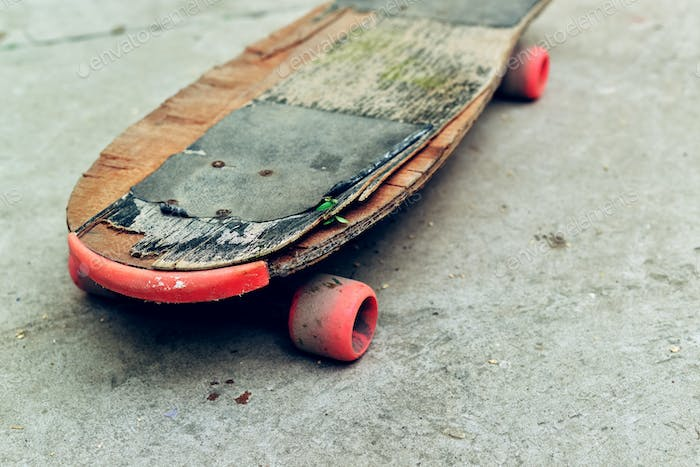 Old weathered skateboard on concrete surface