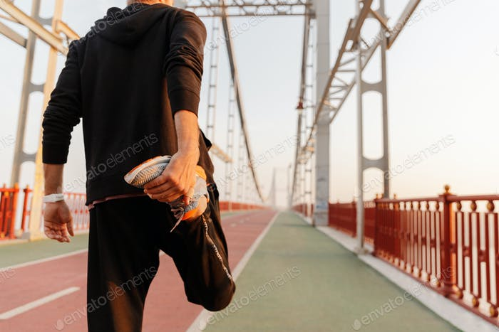 Back view of a young fit sportsman working out on a bridge