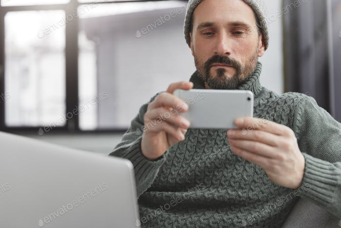 Mature bearded male uses smart phone for making photos, sits in front of laptop computer, uses free